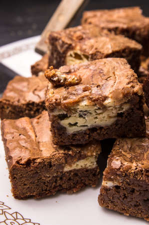 Cream cheese brownies, sliced and stacked on a plate, ready to be served.