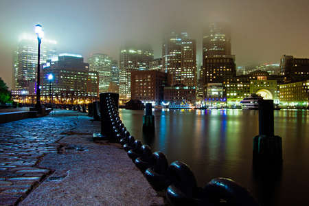 Fog covers Boston Harbor and Downtown Boston at night.