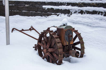 farm equipment: An old piece of rusted farm equipment sits in snow.