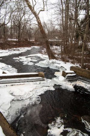 A stream flows over a dam in winter.