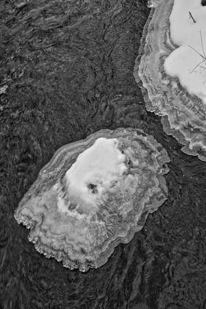 An island of ice sits in a river in winter.