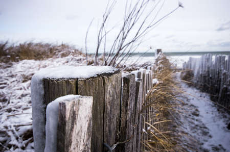 A snow covered path to the beach.