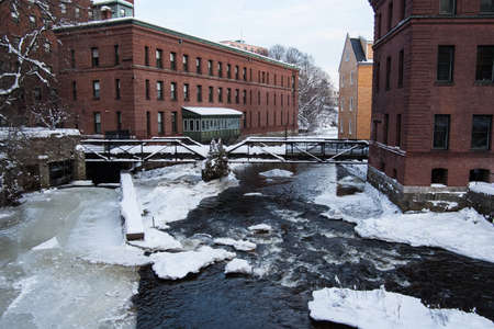 The Neponset River separates Boston from Milton at the Lower Falls.  Old mill buildings line both sides of the river.