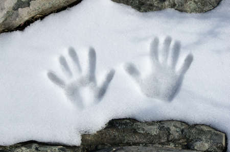 A set of handprints in a patch of snow. Foto de archivo