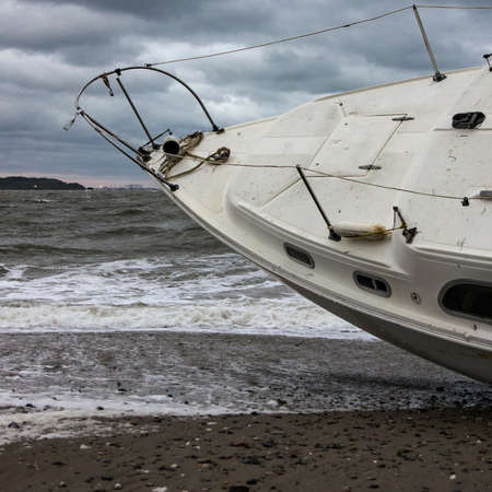 A sailboat washed ashore on the beach in Quincy Ma after a strong storm.