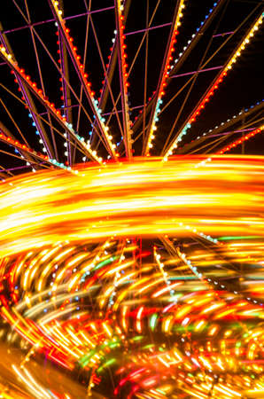 wheel spin: A carousel and ferris wheel spin at a carnival. Stock Photo