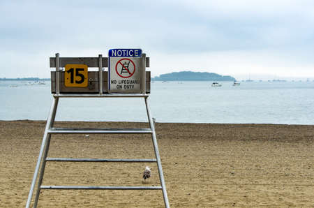 A lifeguard chair sits empty on the beach on a foggy day in Quincy Ma.