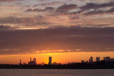 The skyline of Boston at sunset with clouds hanging overhead, as seen from a boat in the harbor. Reklamní fotografie