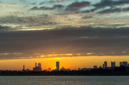 The skyline of Boston at sunset with clouds hanging overhead, as seen from a boat in the harbor. Foto de archivo