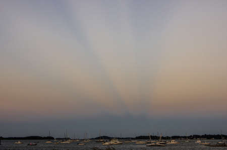 Rays from the sun cut through hazy sky at sunset.