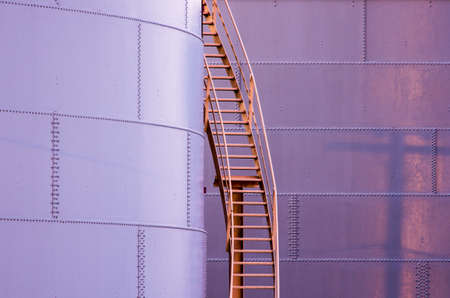 A ladder leads up the side of a storage tank.