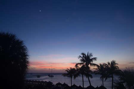The sun sets over the beach in Aruba.