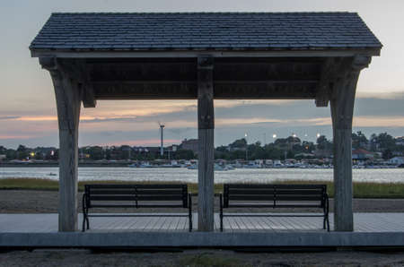 A roof covers benches next to Malibu Beach in Boston MA.
