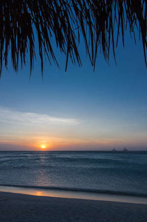 The sun sets over the sea in Aruba.