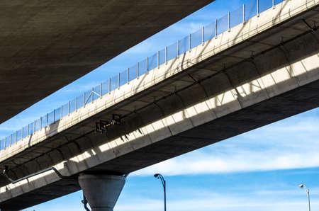A concrete freeway ramp runs overhead.