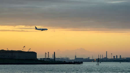 A commercail airliner flying into Boston Logan Airport at sunset.  It's crossing over Castle Island and Boston Harbor.