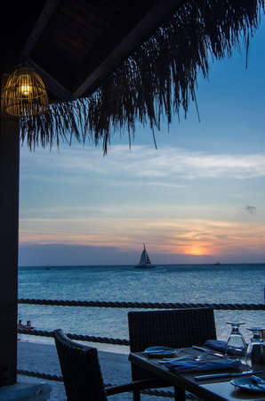 A table is set for dinner at sunset in Aruba. Foto de archivo