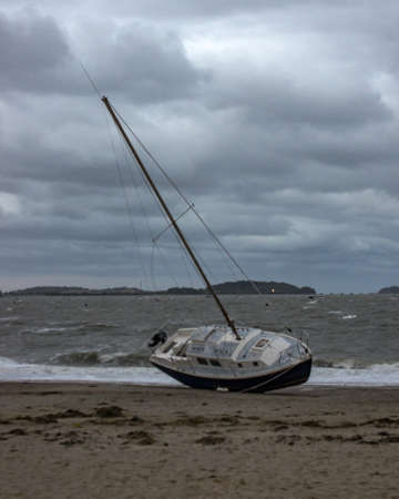 beached: A sailboat washed ashore on the beach in Quincy Ma after a strong storm.