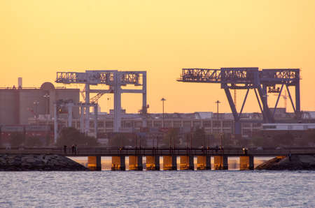 Two shipping cranes in Boston are highlighted by the setting sun.