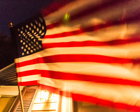 An American flag blows in the wind on a home. Reklamní fotografie