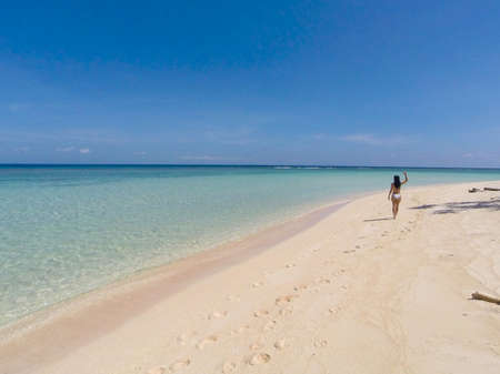 Girl walking on the white beach and turquoise water with clear blue sky on Pink Island in Balabac, Palawan, Philippines