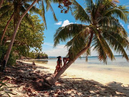Encantadora pareja de pie cerca de palmeras en la paradisíaca isla Onok en Balabac Palawan en Filipinas