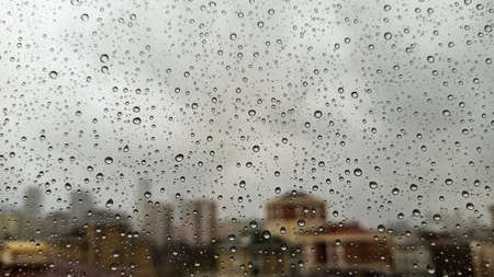 Raindrops on office window with blur gray sky background. Office window covered with closeup rain water. Standard-Bild