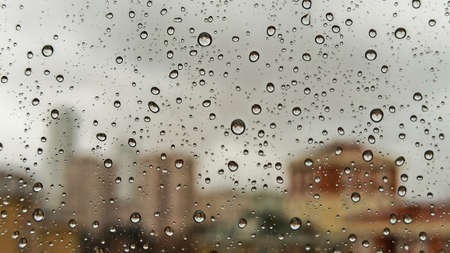 Raindrops on office window with blur gray sky background. Office window covered with closeup rain water.