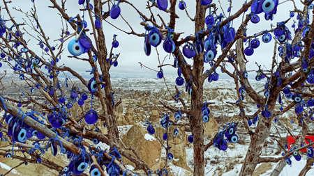 Blue Evil eye charms hang on the tree in Cappadocia, Turkey