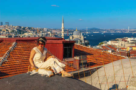 Woman touching yellow cat at the roof with bosphorus background in Istanbul