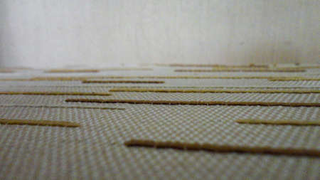 white fabric background with tiny brown lines. Close-up white cotton texture with brown straight lines