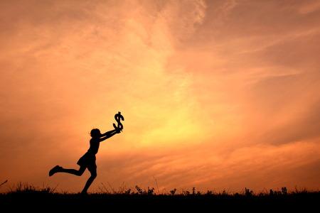 Crianças silhueta segurando dinheiro no pôr do sol.