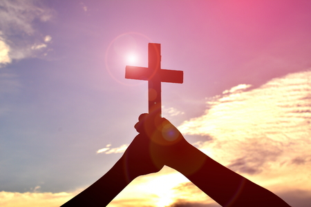 Silhouette hand holding jesus and cross at sunset Stock Photo