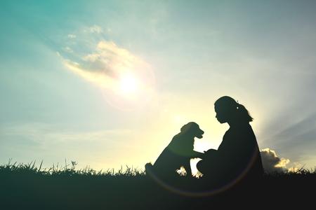 silhueta das mulheres que jogam com cão no por do sol