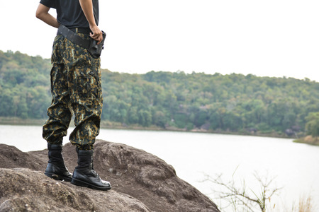 uniform green shoe: Soldier stand on the rock in nature background