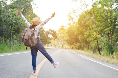 Lo zaino asiatico felice della ragazza nei precedenti della foresta e della strada, si rilassa il tempo sul viaggio di concetto di festa, sul colore del tono d'annata e sul fuoco molle Archivio Fotografico