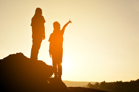 Silhouette of happy women on the rock near the river, color of vintage tone