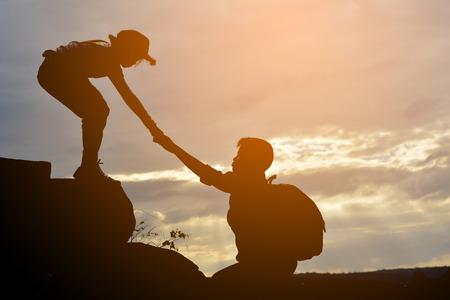 女孩的剪影幫助一個男孩在山上在天空日落