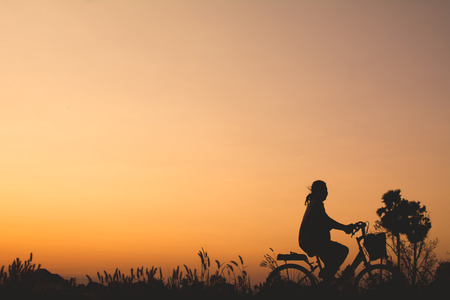 Silhouette of bicycle on grass with the sky sunset