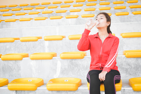 Young women drinking water after exercise in stadium Stock Photo