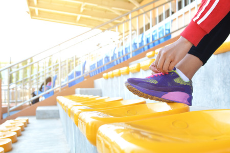 shoelace: Young women shoe laces after exercise in staduim