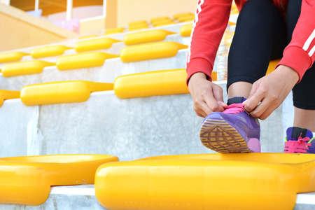 Young women shoe laces after exercise in staduim
