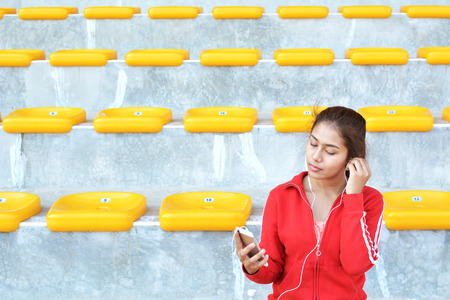 Women listen music in smartphone on stadium after exercise
