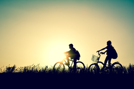 Silhouette of children with bicycle on grass field at the sky sunset, color of vintage tone and soft focus concept journey in holiday. Stock Photo
