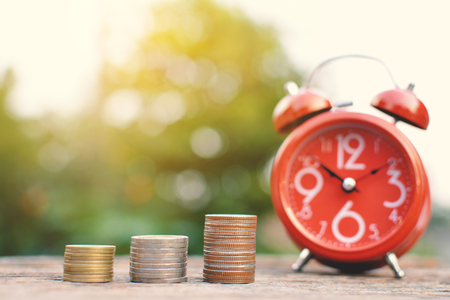 Red alarm clock with coin on old wood tree bokeh background,color of vintage tone selective focus
