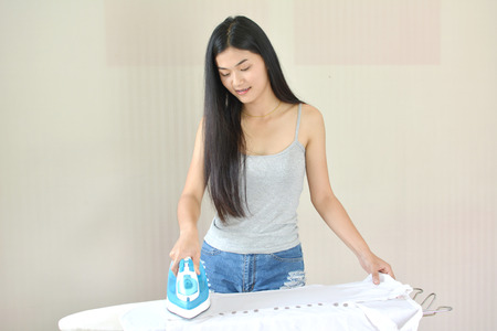 Beautiful young women ironing a shirt in the room at home