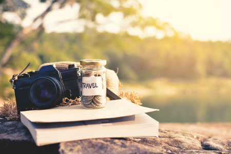 Close up coin on glass jar with travel word and accessories for backpack on stone nature background, color vintage tone