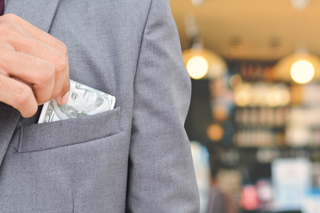 putting money in pocket: Close up businessman hand holding money on blur of focus cafe shop background Stock Photo