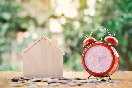 Coins and wood house with red alarm clock on table tree bokeh background concept save money for home ,selective and soft focus vintage tone