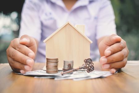 小さな木の家とコイン コンセプトを保持手少年が私のホームの選択とソフト フォーカスのヒップスター トーンのお金を節約します。